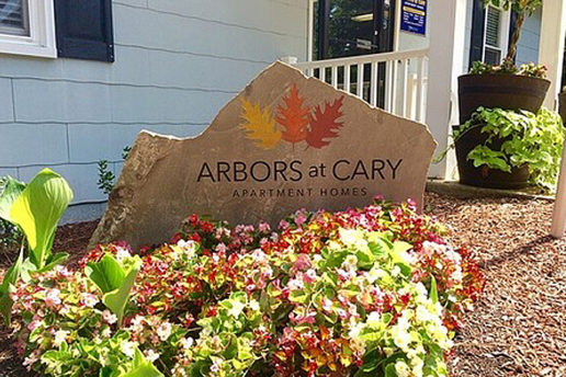 Arbors at Cary Apartment homes stone sign and flowers