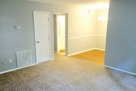 carpeted living room, hard wood floor dining area, white doors, gray walls