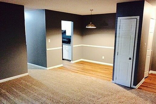 carpeted living room, hard wood floor dining area, white doors, dark gray walls