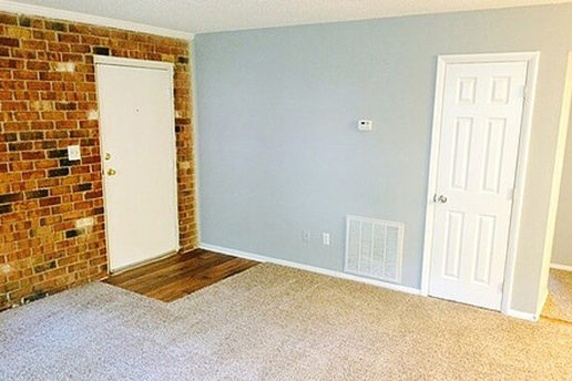 carpeted living room, hard wood floor entry with brick wall, white doors, light gray walls