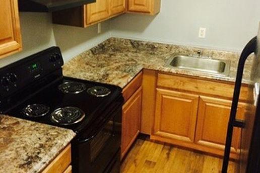 kitchen, brown cabinets, granite countertops, black appliances