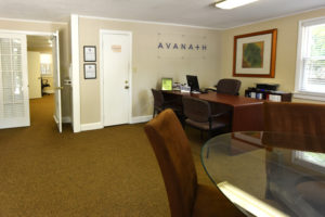 Leasing office with desks and chairs, Avanath logo on wall